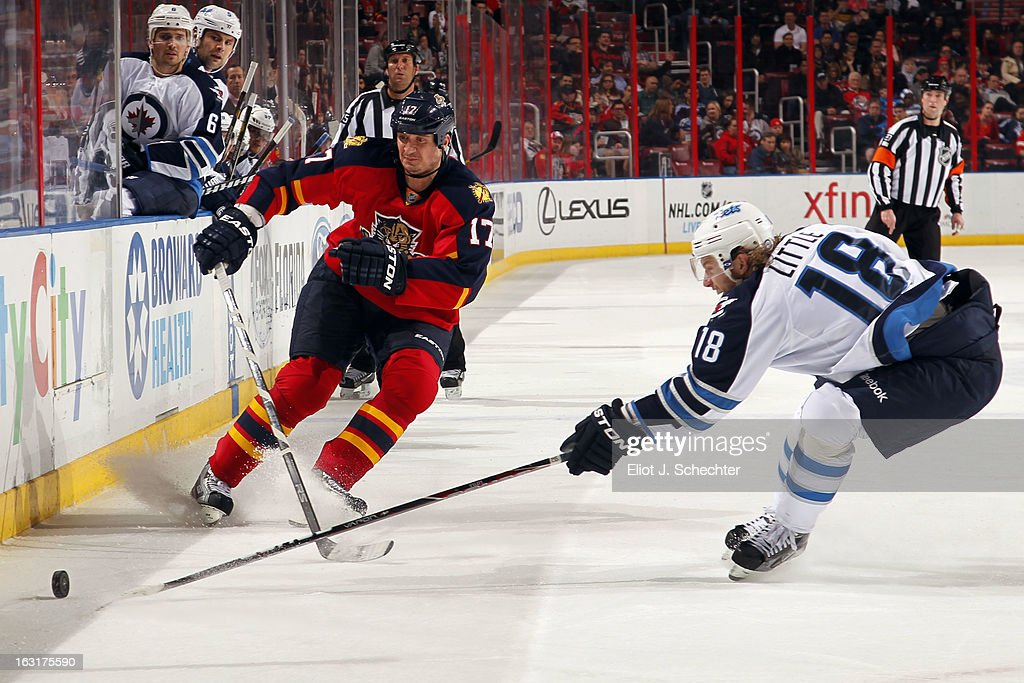 Bryan Little #18 of the Winnipeg Jets digs the puck out from the boards against Filip Kuba #17 of the Florida Panthers at the BB&T Center on March 5, 2013 in Sunrise, Florida.