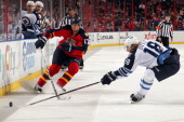 Bryan Little of the Winnipeg Jets digs the puck out from the boards against Filip Kuba of the Florida Panthers at the BBT Center on March 5 2013 in...