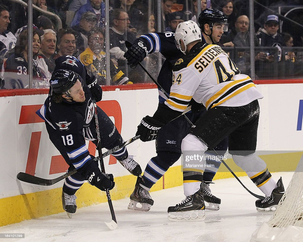 Bryan Little #18 of the Winnipeg Jets falls against the boards while Andrew Ladd #16 and Dennis Seidenberg #44 of the Boston Bruins get back to the play during second period action on March 19, 2013 at the MTS Centre in Winnipeg, Manitoba, Canada.