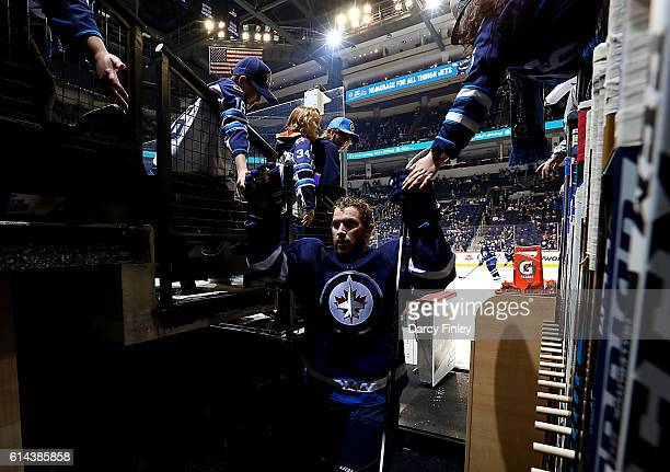 Bryan Little of the Winnipeg Jets fist bumps fans as he leaves the ice following the pregame warm up prior to NHL action against the Carolina...