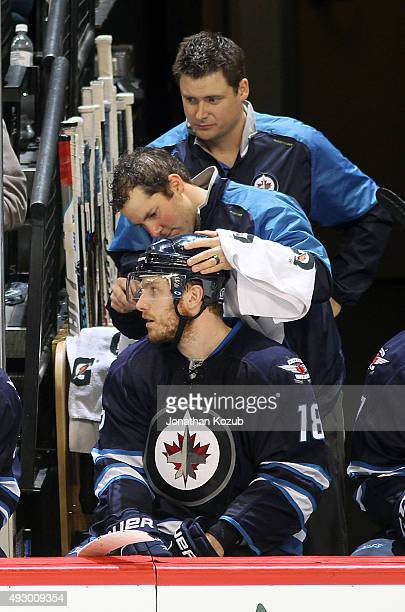 Bryan Little of the Winnipeg Jets gets an equipment adjustment during second period action against the Calgary Flames at the MTS Centre on October 16...