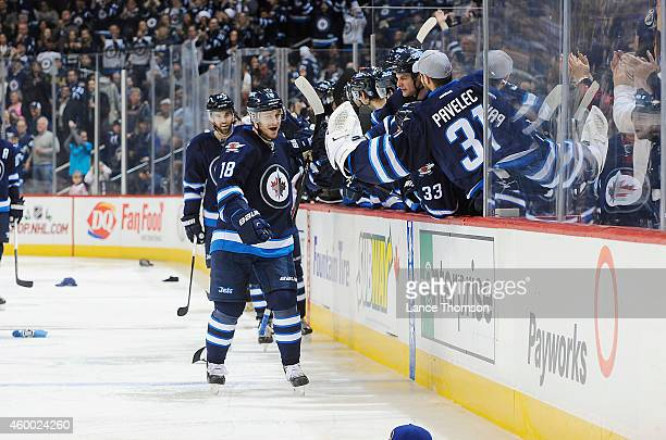 Bryan Little of the Winnipeg Jets gets congratulated by teammates at the bench after scoring his hat trick goal against the Colorado Avalanche on...