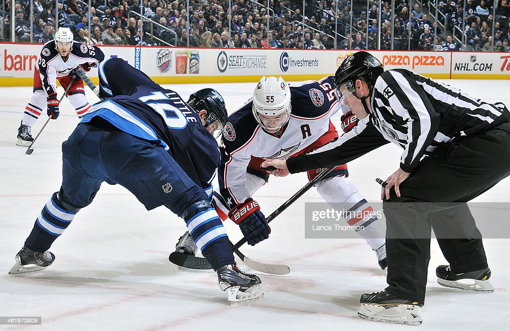 <a gi-track='captionPersonalityLinkClicked' href=/galleries/search?phrase=Bryan+Little&family=editorial&specificpeople=540533 ng-click='$event.stopPropagation()'>Bryan Little</a> #18 of the Winnipeg Jets gets set for a third period face-off against <a gi-track='captionPersonalityLinkClicked' href=/galleries/search?phrase=Mark+Letestu&family=editorial&specificpeople=4601071 ng-click='$event.stopPropagation()'>Mark Letestu</a> #55 of the Columbus Blue Jackets at the MTS Centre on January 11, 2014 in Winnipeg, Manitoba, Canada.