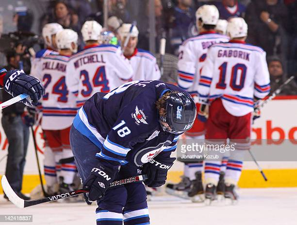 Bryan Little of the Winnipeg Jets hangs his head in dejection as he skates off the ice while members of the New York Rangers celebrate a 42 victory...