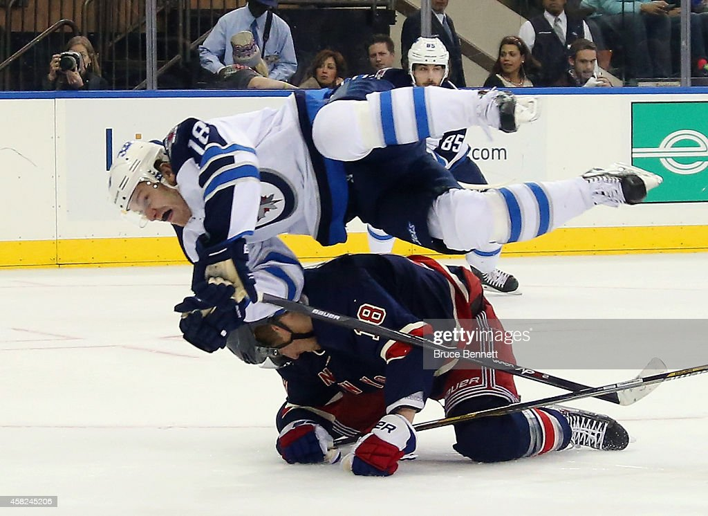<a gi-track='captionPersonalityLinkClicked' href=/galleries/search?phrase=Bryan+Little&family=editorial&specificpeople=540533 ng-click='$event.stopPropagation()'>Bryan Little</a> #18 of the Winnipeg Jets hurdles over <a gi-track='captionPersonalityLinkClicked' href=/galleries/search?phrase=Marc+Staal&family=editorial&specificpeople=3809026 ng-click='$event.stopPropagation()'>Marc Staal</a> #18 of the New York Rangers during the first period at Madison Square Garden on November 1, 2014 in New York City.
