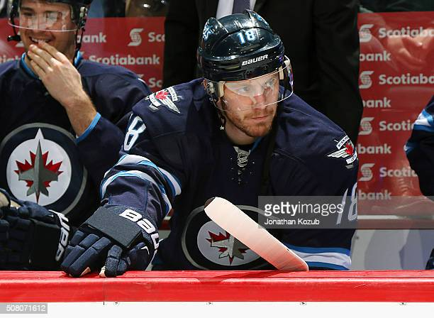 Bryan Little of the Winnipeg Jets looks on from the bench prior to puck drop against the Dallas Stars at the MTS Centre on February 2 2016 in...