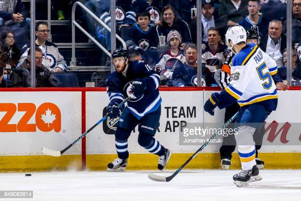 Bryan Little of the Winnipeg Jets plays the puck along the boards as Magnus Paajarvi of the St Louis Blues defends during first period action at the...