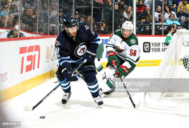 Bryan Little of the Winnipeg Jets plays the puck around the net as Erik Haula of the Minnesota Wild gives chase during second period action at the...