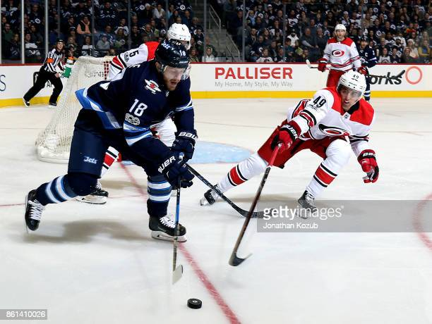 Bryan Little of the Winnipeg Jets plays the puck as Victor Rask of the Carolina Hurricanes defends during second period action at the Bell MTS Place...