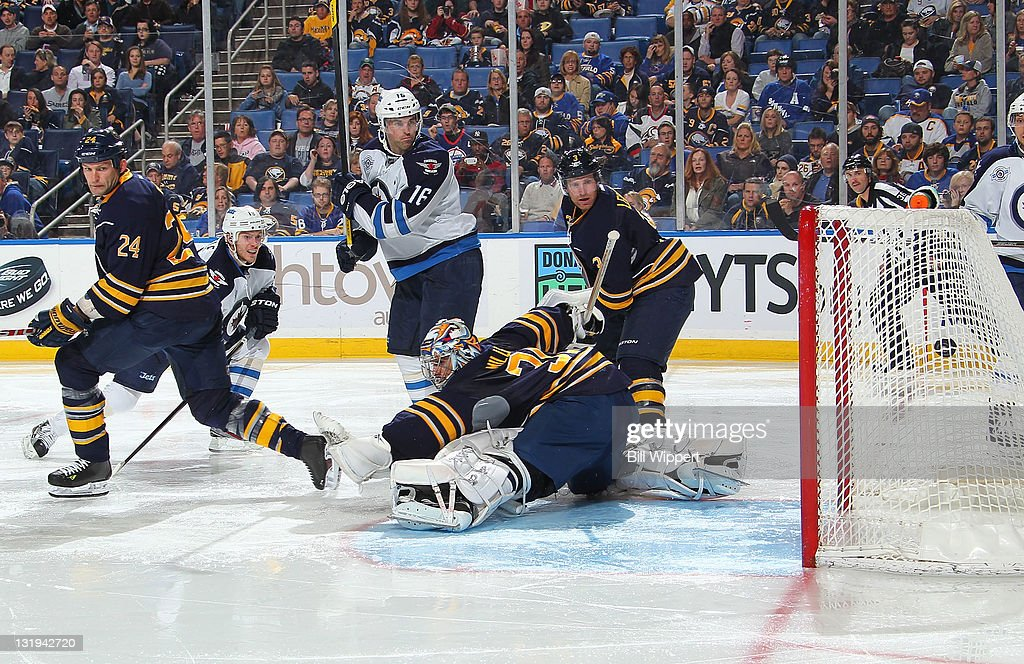 Bryan Little #18 of the Winnipeg Jets scores a second-period goal as teammate <a gi-track='captionPersonalityLinkClicked' href=/galleries/search?phrase=Andrew+Ladd&family=editorial&specificpeople=228452 ng-click='$event.stopPropagation()'>Andrew Ladd</a> #16 looks on against Ryan Miller #30 and <a gi-track='captionPersonalityLinkClicked' href=/galleries/search?phrase=Robyn+Regehr&family=editorial&specificpeople=171828 ng-click='$event.stopPropagation()'>Robyn Regehr</a> #24 of the Buffalo Sabres at First Niagara Center on November 8, 2011 in Buffalo, New York.
