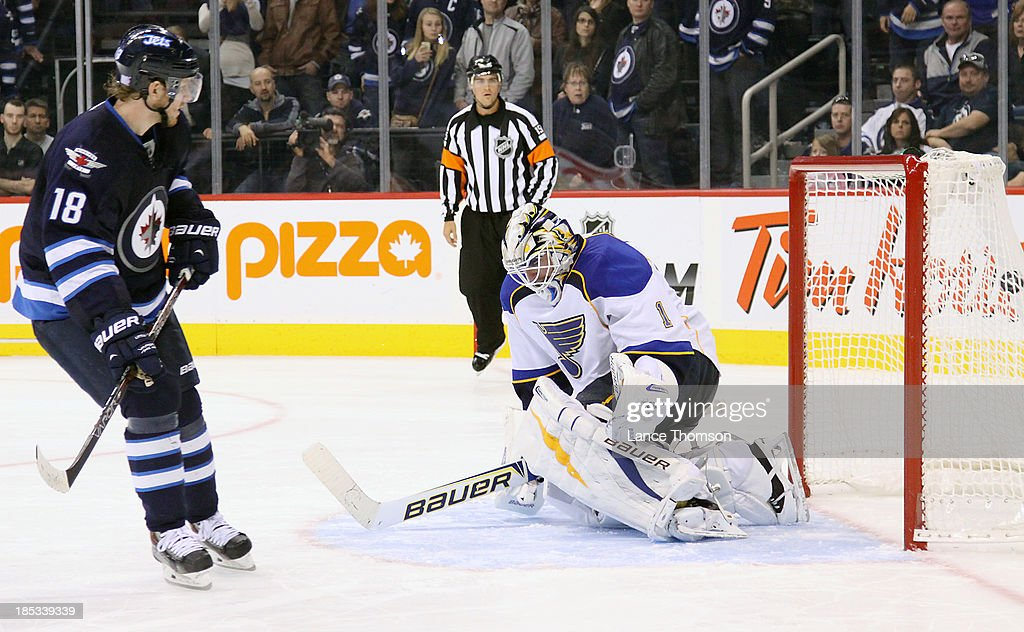 <a gi-track='captionPersonalityLinkClicked' href=/galleries/search?phrase=Bryan+Little&family=editorial&specificpeople=540533 ng-click='$event.stopPropagation()'>Bryan Little</a> #18 of the Winnipeg Jets scores against goaltender <a gi-track='captionPersonalityLinkClicked' href=/galleries/search?phrase=Brian+Elliott&family=editorial&specificpeople=687032 ng-click='$event.stopPropagation()'>Brian Elliott</a> #1 of the St. Louis Blues during a shootout at the MTS Centre on October 18, 2013 in Winnipeg, Manitoba, Canada. The Jets won the game 4-3.