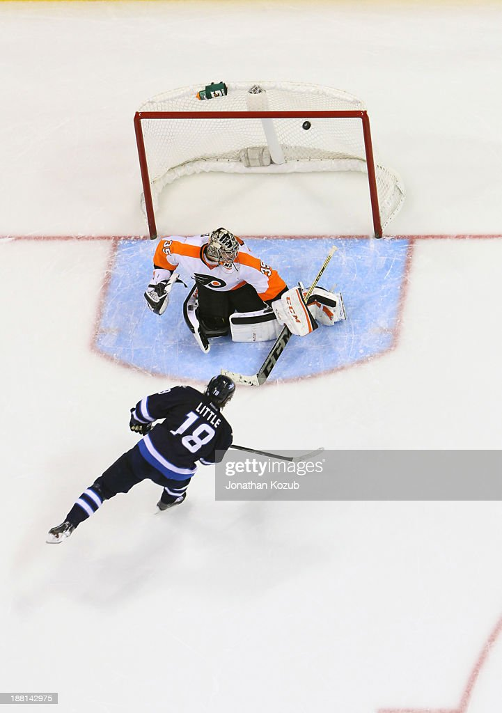 <a gi-track='captionPersonalityLinkClicked' href=/galleries/search?phrase=Bryan+Little&family=editorial&specificpeople=540533 ng-click='$event.stopPropagation()'>Bryan Little</a> #18 of the Winnipeg Jets shoots the puck over the shoulder of goaltender Steve Mason #35 of the Philadelphia Flyers during the shootout at the MTS Centre on November 15, 2013 in Winnipeg, Manitoba, Canada. The Jets defeated the Flyers 3-2.