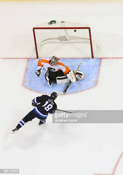 Bryan Little of the Winnipeg Jets shoots the puck over the shoulder of goaltender Steve Mason of the Philadelphia Flyers during the shootout at the...