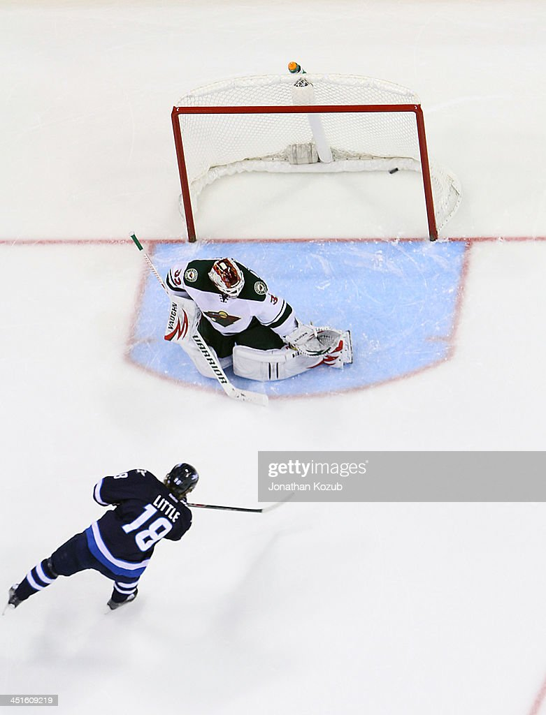 <a gi-track='captionPersonalityLinkClicked' href=/galleries/search?phrase=Bryan+Little&family=editorial&specificpeople=540533 ng-click='$event.stopPropagation()'>Bryan Little</a> #18 of the Winnipeg Jets shoots the puck over the shoulder of goaltender <a gi-track='captionPersonalityLinkClicked' href=/galleries/search?phrase=Niklas+Backstrom&family=editorial&specificpeople=861018 ng-click='$event.stopPropagation()'>Niklas Backstrom</a> #32 of the Minnesota Wild during the shootout at the MTS Centre on November 23, 2013 in Winnipeg, Manitoba, Canada. The Wild defeated the Jets 3-2.