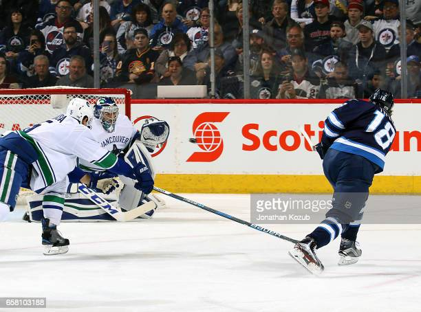 Bryan Little of the Winnipeg Jets shoots the puck over the stick of a defending Luca Sbisa of the Vancouver Canucks as goaltender Ryan Miller guards...
