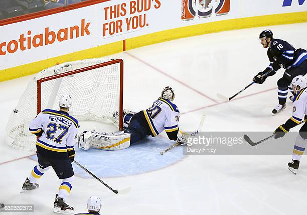Bryan Little of the Winnipeg Jets shoots the puck past a sprawling Pheonix Copley of the St Louis Blues for a third period goal at the MTS Centre on...
