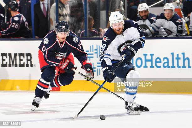Bryan Little of the Winnipeg Jets skates the puck away from Brandon Saad of the Columbus Blue Jackets during the second period of a game on April 6...