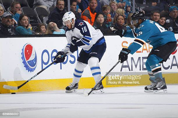 Bryan Little of the Winnipeg Jets skates with the puck against Joel Ward of the San Jose Sharks at SAP Center on January 16 2017 in San Jose...