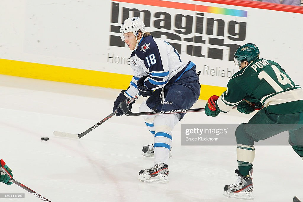<a gi-track='captionPersonalityLinkClicked' href=/galleries/search?phrase=Bryan+Little&family=editorial&specificpeople=540533 ng-click='$event.stopPropagation()'>Bryan Little</a> #18 of the Winnipeg Jets skates with the puck with <a gi-track='captionPersonalityLinkClicked' href=/galleries/search?phrase=Darroll+Powe&family=editorial&specificpeople=4527845 ng-click='$event.stopPropagation()'>Darroll Powe</a> #14 of the Minnesota Wild defends during the game at the Xcel Energy Center on February 16, 2012 in St. Paul, Minnesota.