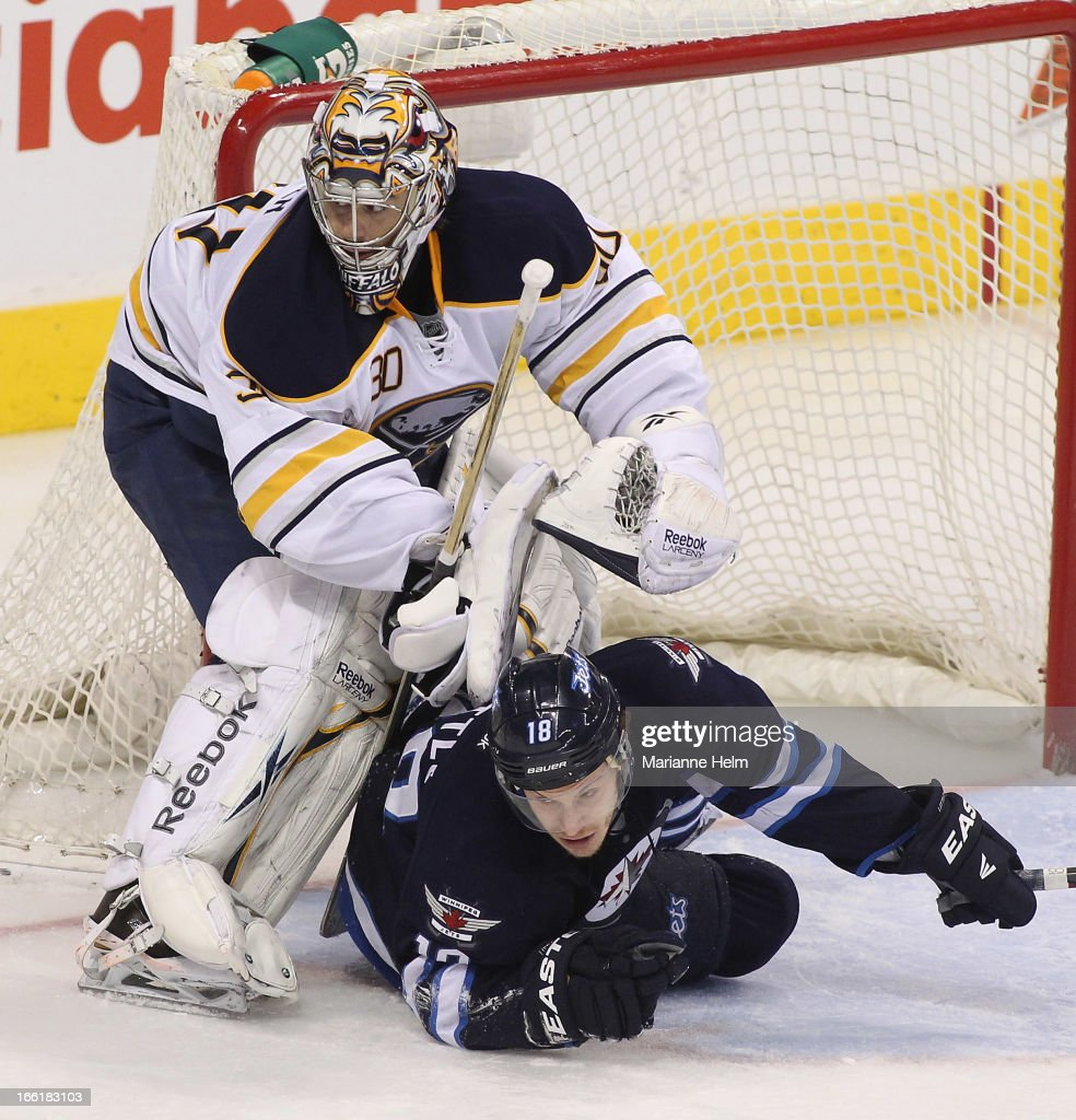 Bryan Little #18 of the Winnipeg Jets slides underneath goalie Ryan Miller #30 of the Buffalo Sabres during third-period action on April 9, 2013 at the MTS Centre in Winnipeg, Manitoba, Canada.
