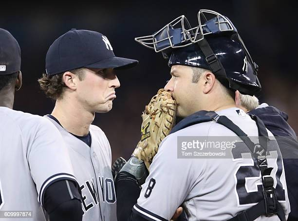 Bryan Mitchell of the New York Yankees reacts during a visit to the mound by pitching coach Larry Rothschild and Austin Romine in the third inning...