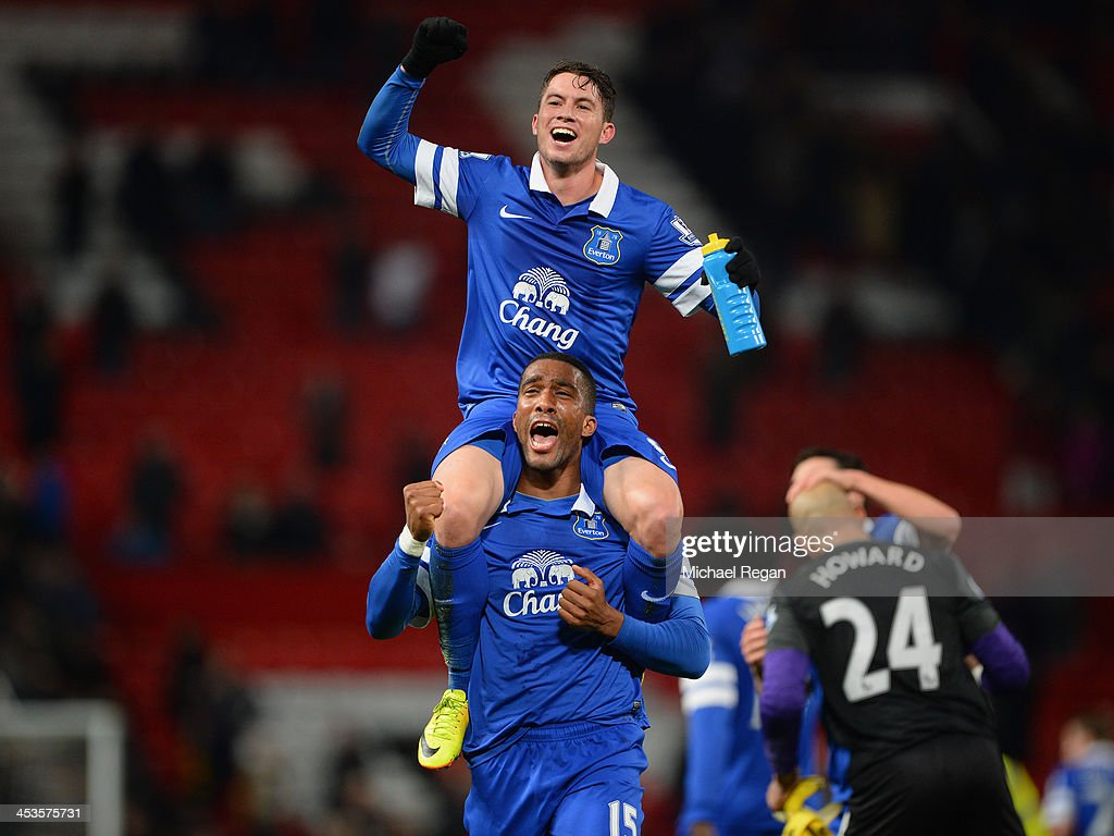 Bryan Oviedo of Everton (top) celebrates with team-mate Sylvain Distin at the end of the Barclays Premier League match between Manchester United and Everton at Old Trafford on December 4, 2013 in Manchester, England.