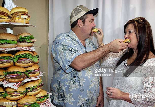 Bryan Porter and Darlene Hieslcher eat from their burger cake following the first wedding ceremony of 11/12/13 officiated by Elvis at Smashburger on...