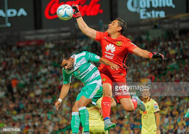 Bryan Rabello of Santos and Moises Muñoz goalkeeper of America jump for the ball during a 5th round match between Santos Laguna and America as part...