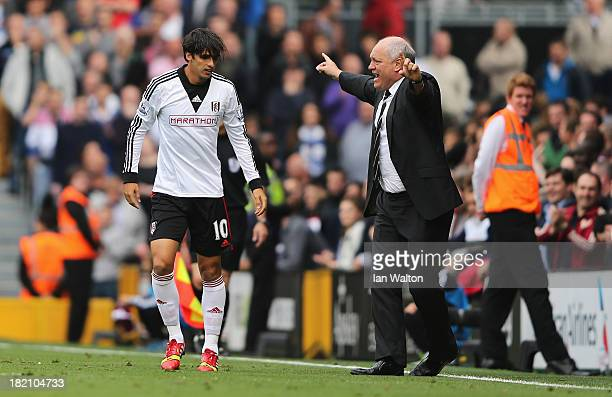Bryan Ruiz of Fulham celebrates his goal with manager Martin Jol during the Barclays Premier League match between Fulham and Cardiff City at Craven...