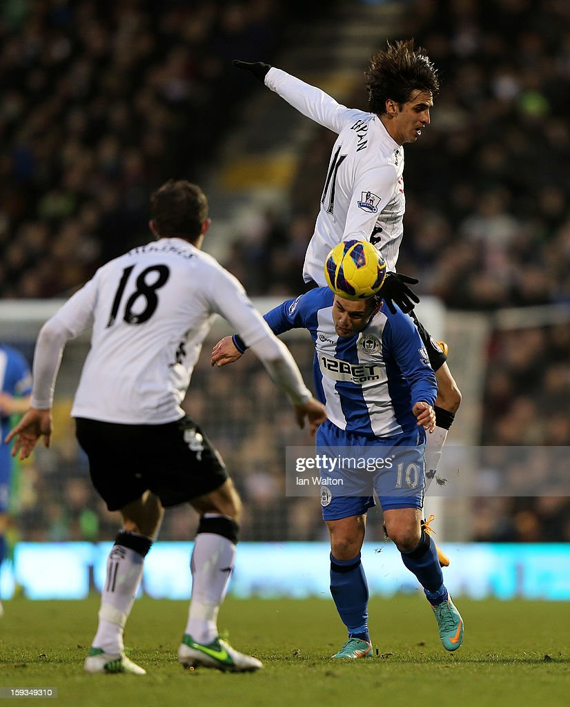 Bryan Ruiz of Fulham rises above Shaun Maloney of Wigan to win a header during the Barclays Premier League match between Fulham and Wigan Athletic at Craven Cottage on January 12, 2013 in London, England.