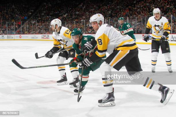 Bryan Rust Brian Dumoulin of the Pittsburgh Penguins skate to the puck against Luke Kunin of the Minnesota Wild during the game at the Xcel Energy...