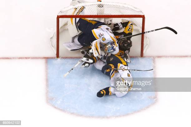 Bryan Rust of the Pittsburgh Penguins and Roman Josi collide with Pekka Rinne of the Nashville Predators during the first period in Game Five of the...