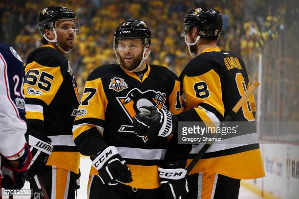 Bryan Rust of the Pittsburgh Penguins celebrates his secondperiod goal with Brian Dumoulin and Ron Hainsey while playing the Columbus Blue Jackets in...