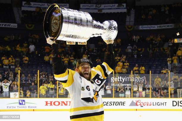 Bryan Rust of the Pittsburgh Penguins celebrates with the Stanley Cup trophy after defeating the Nashville Predators 20 in Game Six of the 2017 NHL...