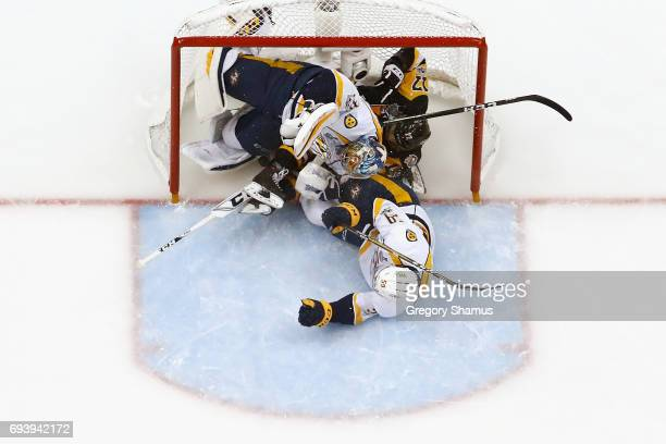 Bryan Rust of the Pittsburgh Penguins collides with Pekka Rinne and Roman Josi of the Nashville Predators in the first period in Game Five of the...