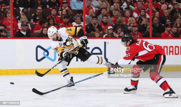 Bryan Rust of the Pittsburgh Penguins fires a shot with pressure from Erik Karlsson of the Ottawa Senators in Game Six of the Eastern Conference...