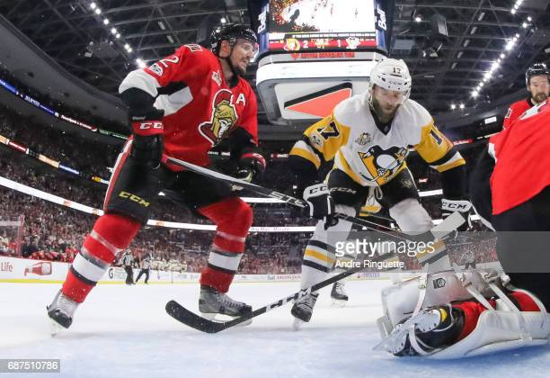 Bryan Rust of the Pittsburgh Penguins grabs the stick of Dion Phaneuf of the Ottawa Senators outside the crease in Game Six of the Eastern Conference...