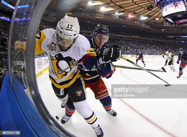 Bryan Rust of the Pittsburgh Penguins is checke into the boards by Brady Skjei of the New York Rangers during the first period at Madison Square...