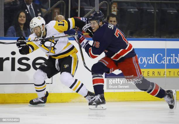 Bryan Rust of the Pittsburgh Penguins is slowed down by Brady Skjei of the New York Rangers during the first period at Madison Square Garden on March...