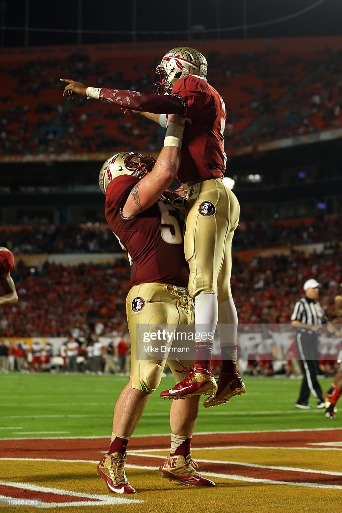 Bryan Stork #52 and EJ Manuel #3 of the Florida State Seminoles celebrate after Manuel scored a 9-yard rushing touchdown in the fourth quarter against the Northern Illinois Huskies during the Discover Orange Bowl at Sun Life Stadium on January 1, 2013 in Miami Gardens, Florida.