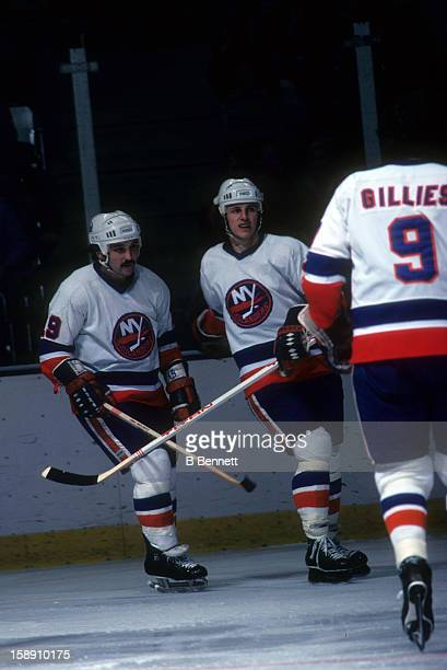 Bryan Trottier and Mike Bossy of the New York Islanders celebrate as Clark Gillies joins in during an NHL game in January 1979 at the Nassau Coliseum...