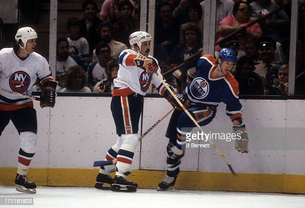 Bryan Trottier of the New York Islanders checks Kevin Lowe of the Edmonton Oilers during the 1984 Stanley Cup Finals in May 1984 at the Nassau...