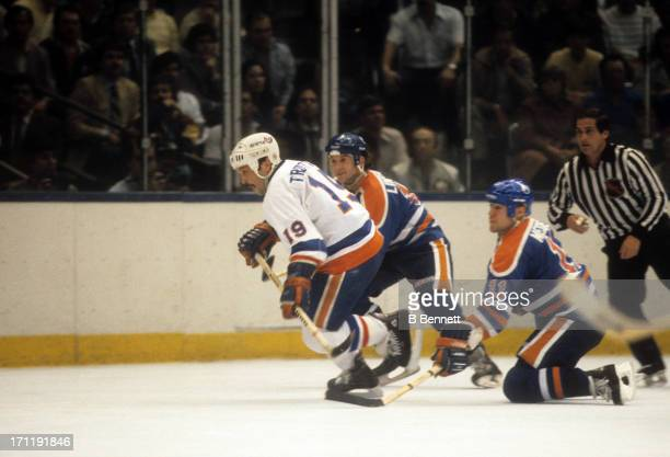 Bryan Trottier of the New York Islanders skates on the ice as Mark Messier and Ken Linesman of the Edmonton Oilers follow behind during the 1984...