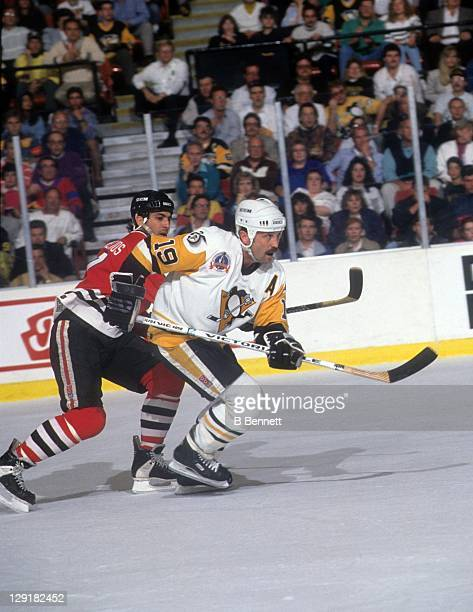 Bryan Trottier of the Pittsburgh Penguins and Chris Chelios of the Chicago Blackhawks go for the puck during Game 1 of the 1992 Stanley Cup Finals on...