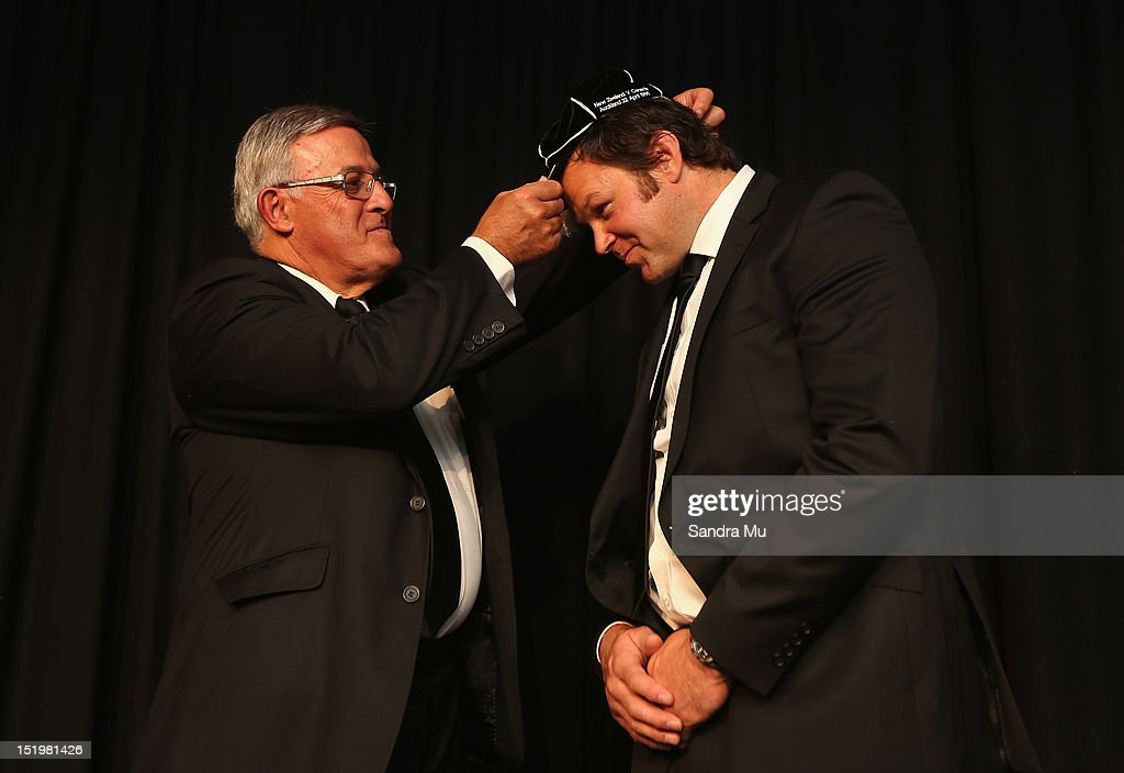 Bryan Williams, president of the New Zealand Rugby Union (L) caps former All Black <a gi-track='captionPersonalityLinkClicked' href=/galleries/search?phrase=Josh+Kronfeld&family=editorial&specificpeople=226635 ng-click='$event.stopPropagation()'>Josh Kronfeld</a> during the New Zealand All Blacks reunion dinner on September 14, 2012 in Dunedin, New Zealand.