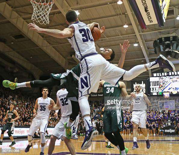 Bryant McIntosh of the Northwestern Wildcats blocks a shot by Bryn Forbes of the Michigan State Spartans at WelshRyan Arena on January 28 2016 in...