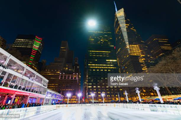 Bryant Park Ice Skating Link, which is illuminated and surrounded by Midtown Manhattan skyscrapers in the night.