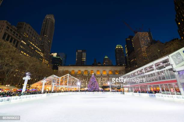 Bryant Park Ice Skating Link, which is illuminated and surrounded by Midtown Manhattan skyscrapers in the night. A Christmas tree stands at front of New York City Library.