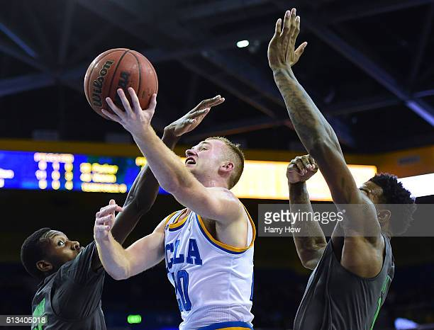 Bryce Alford of the UCLA Bruins is fouled by Chris Boucher of the Oregon Ducks as he attempts a layup in front of Jordan Bell during the first half...