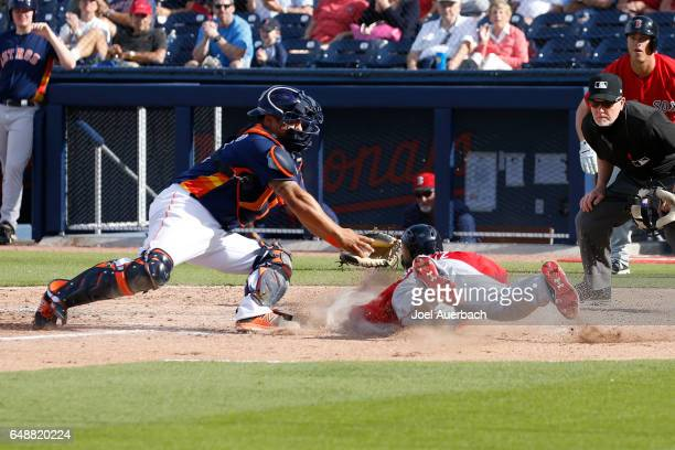 Bryce Brentz of the Boston Red Sox scores past the tag of Juan Centeno of the Houston Astros in the eighth inning during a spring training game at...